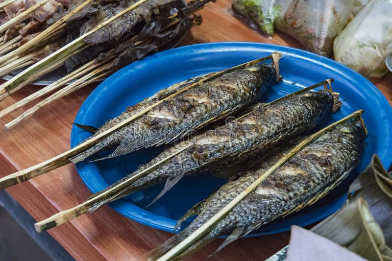 Fried fish in salt on grill on the counter of a market trader. Traditional Asian street food royalty free stock photography