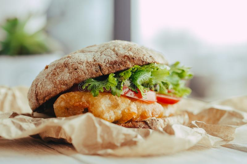 Fried fish Sandwich with lettuce, tomato with tartar sauce. author`s recipe street food royalty free stock photo