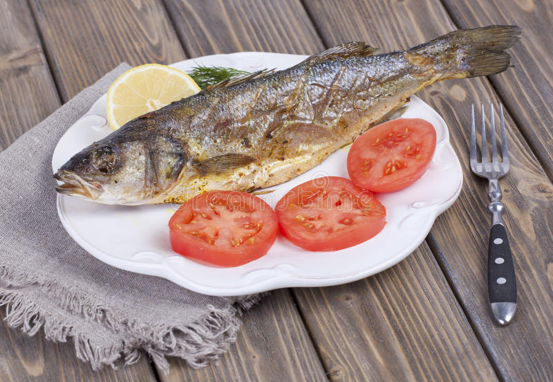 Fried fish sea bass. With lemon and tomato on white plate stock image