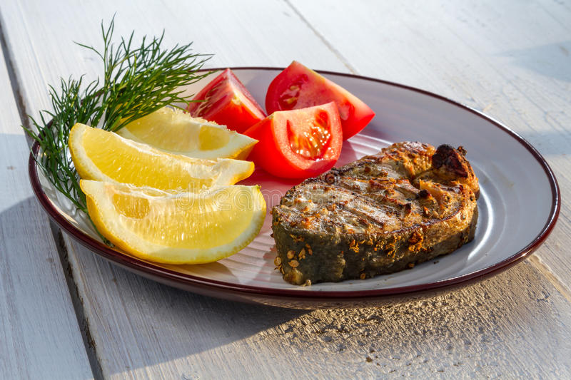 Fried fish served with tomatoes stock photography