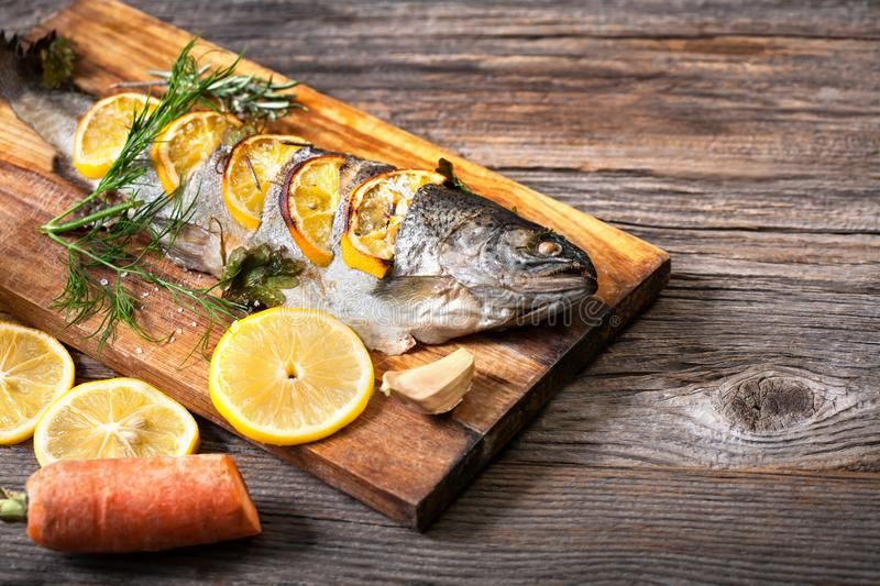 Fried fish with a slice of lemon and vegetables royalty free stock image