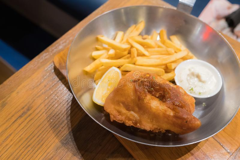 Fried fish steak served with french fries and tartar sauce in a deep pan placed. On a wooden board stock image