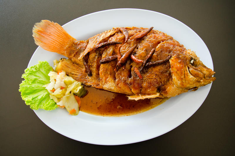 Fried fish topped with sweet sauce. But with hot spices stock images