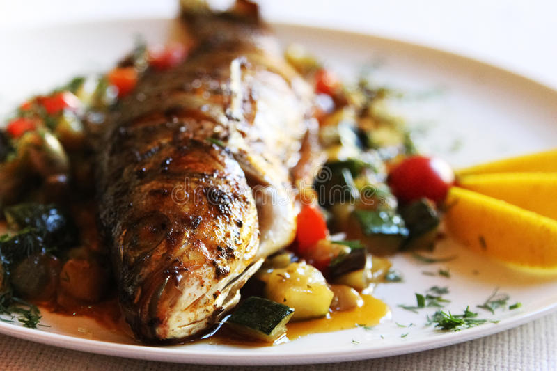 Fried fish with vegetables stock photography