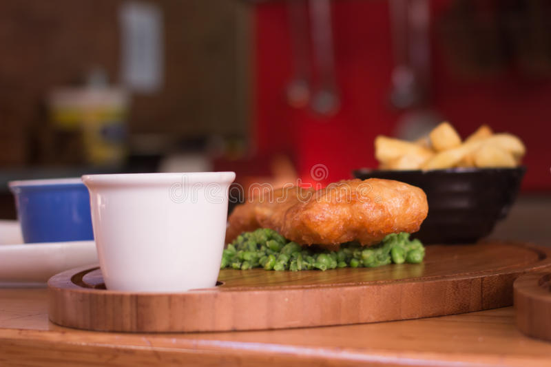 Fried fish wih pies and chips in background. Fish and chips on a pies bed served in english pub royalty free stock photos