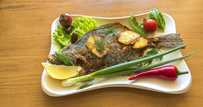 Fried flatfish or flounder served with vegetables and greens stock images