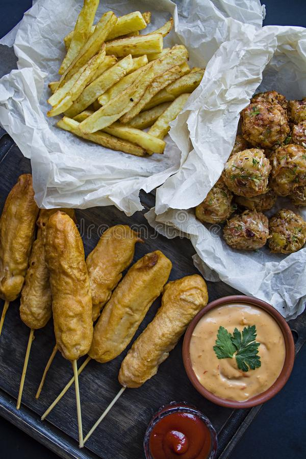 Fried french fries, Ð¡orn Dog and cabbage croquettes and potatoes with sauce and ketchup are decorated with fresh vegetables and stock photo
