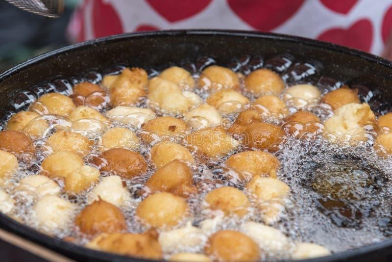 Fried Fritule no óleo quente imagem de stock royalty free