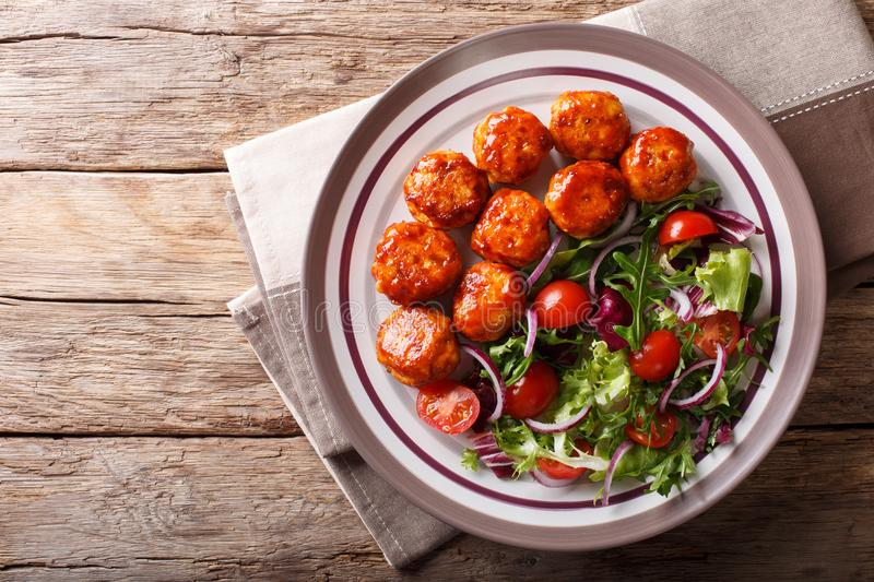 fried glazed meatballs served with salad of lettuce, cherry tomatoes and onions close-up on a plate. Horizontal top view stock image
