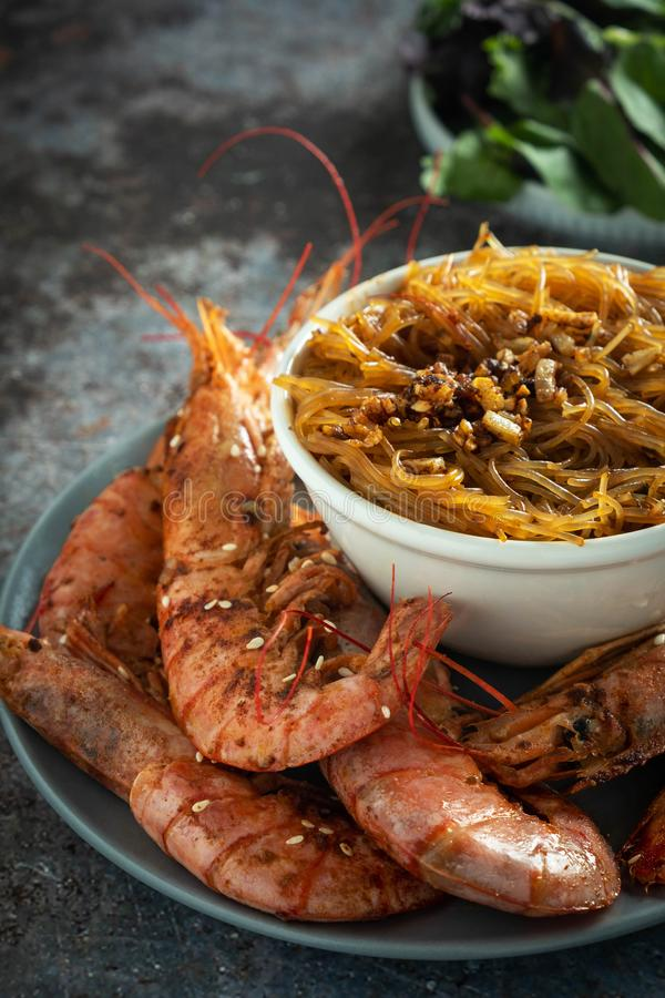 Fried grilled prawns with rice noodle, sauce and lettuce, dark background stock image