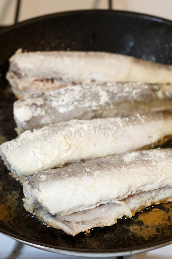 Fried hake fish fillet in a frying pan royalty free stock photography