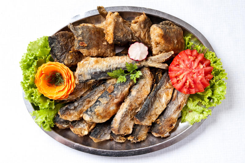Fried herring dish. Elegant plate of delicious food - fried herring pieces garnished with carrot and tomatoes royalty free stock image