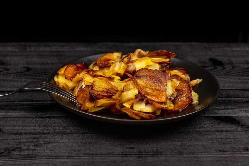 Fried homemade potato chips in a black plate on a wooden rustic background stock images