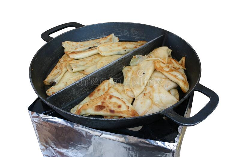 Fried hot pancakes with meat and mushrooms in a large cast-iron pan isolated. On white stock images