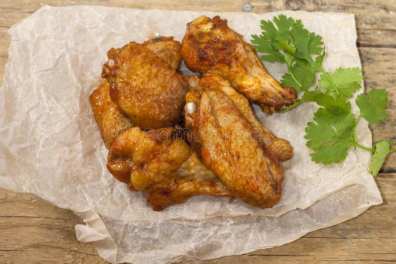 Fried juicy chicken wings marinated with honey, soy sauce, spices with a cilantro branch on a paper background. Asian recipe, top royalty free stock images