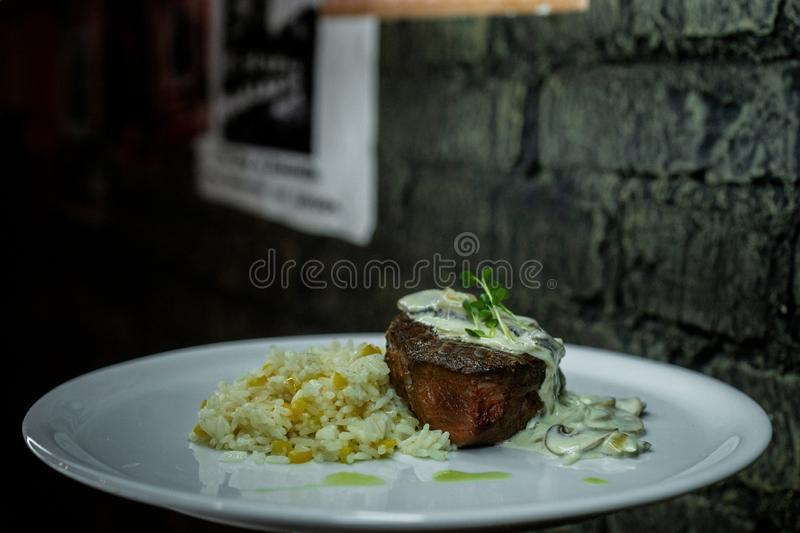Fried juicy meat in creamy mushroom champignon sauce with boiled delicious rice. Excellent full healthy lunch in a restaurant. stock images