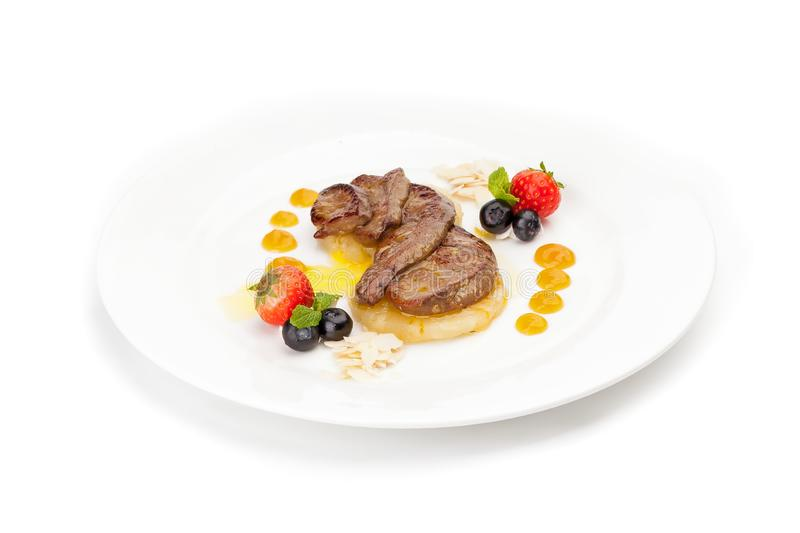 Fried juicy pieces of liver on a piece of pineapple royalty free stock photos