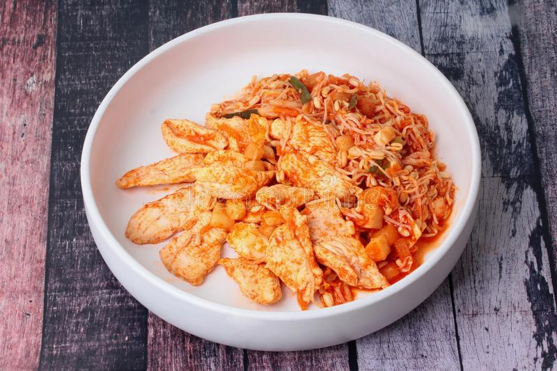 Fried kimji with skinless chicken in korean white plate. Served on wood stock photography