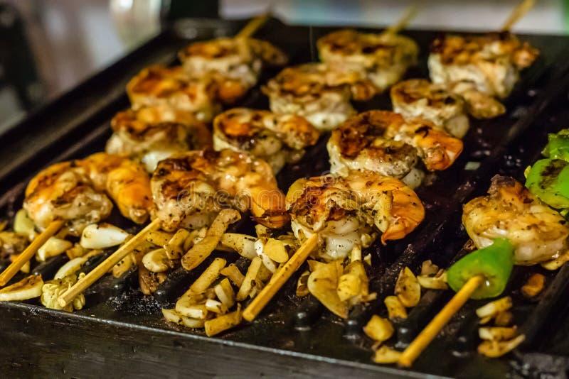 Fried king prawns large appetizing seafood chunks of garlic green chili pepper background culinary stock photo