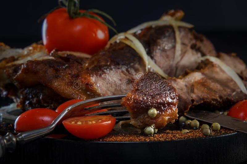 Fried lamb with vegetables. Fried meat on a black background. Piece of meat on the fork. BBQ. Closeup stock image