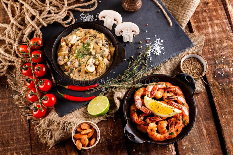 Fried large shrimp in tomato sauce with olive oil,Mushrooms in cream sauce, julienne, champignon, products for cooking stock images