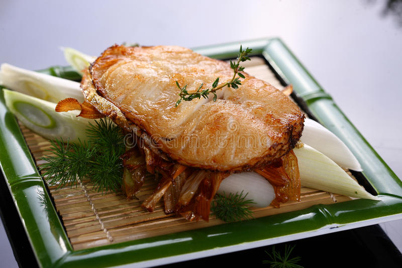 Fried loin of cod with onion on bamboo tray in restaurant stock photo