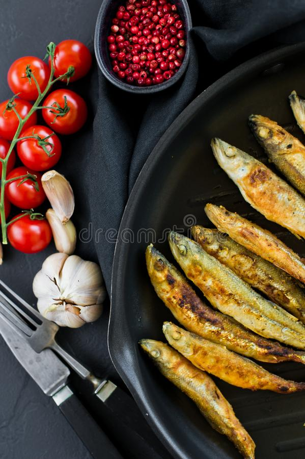 Fried mackerel in a pan. Black background, top view, space for text stock photos