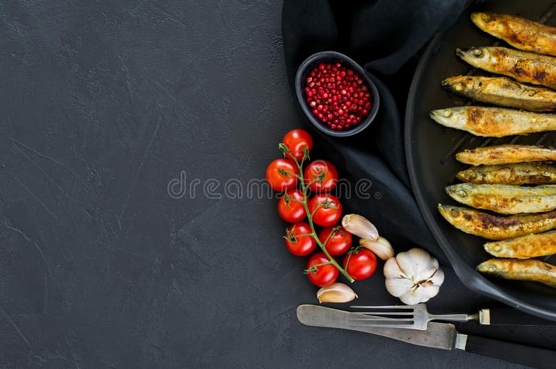Fried mackerel in a pan. Black background, top view, space for text royalty free stock photography