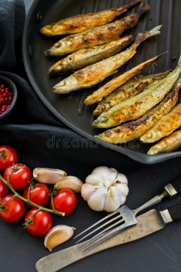 Fried mackerel in a pan. Black background, top view, space for text stock image
