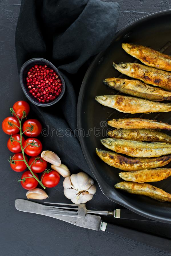 Fried mackerel in a pan. Black background, top view, space for text royalty free stock photo