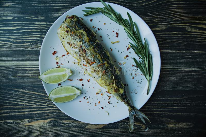 Fried mackerel served on a plate, decorated with spices, herbs and vegetables. Proper nutrition. View from above. Dark wooden royalty free stock image