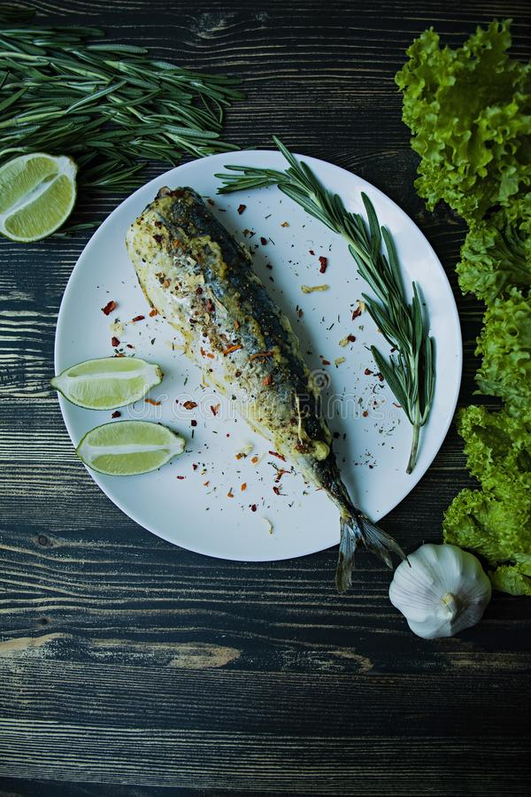Fried mackerel served on a plate, decorated with spices, herbs and vegetables. Proper nutrition. View from above. Dark wooden stock photos