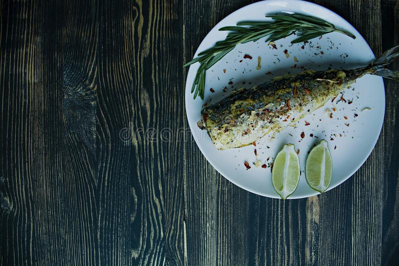 Fried mackerel served on a plate, decorated with spices, herbs and vegetables. Proper nutrition. View from above. Dark wooden royalty free stock images