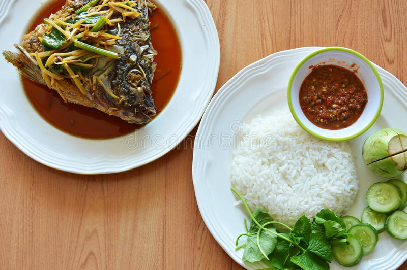 Fried mango fish head dressing ginger soy sauce eat with rice and spicy shrimp paste sauce. In cup stock photo
