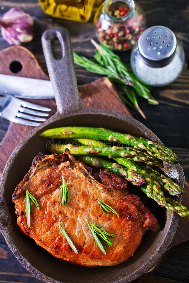 Fried meat. With asparagus in the pan royalty free stock photography