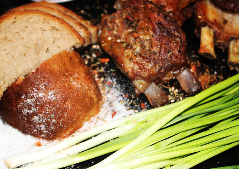 Fried meat on a bone with spices stock photo