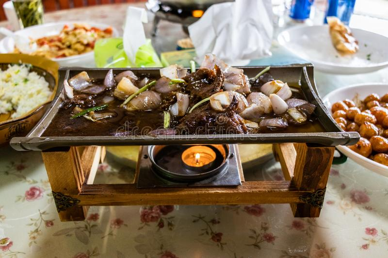 Fried meat and vegetables on a ceramic dish, is heated on a wooden stand. Juicy meat, fried onions, potatoes. stock photos