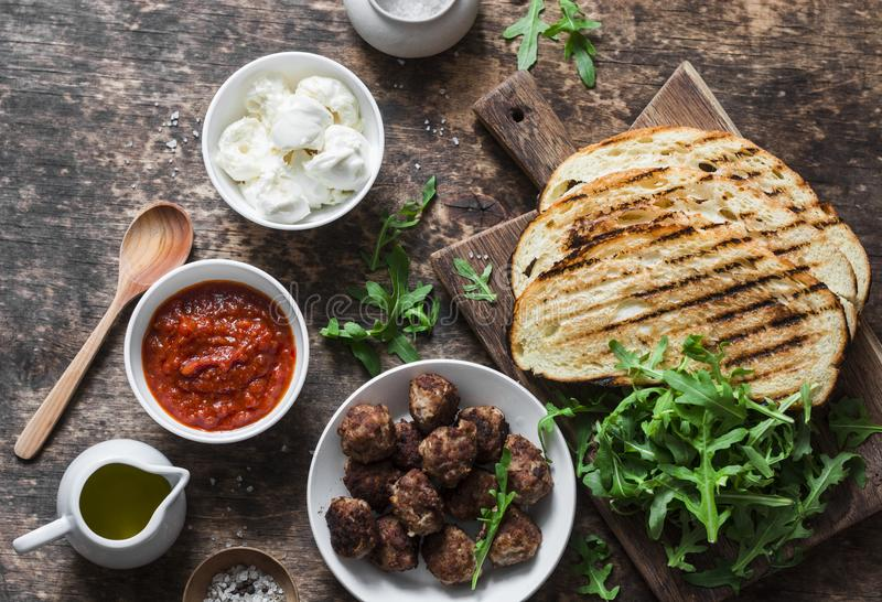 Fried meatballs, tomato sauce, mozzarella, arugula, grilled bread hot sandwiches ingredients on a wooden table, top view. Deliciou. S snack, breakfast, appetizer royalty free stock images