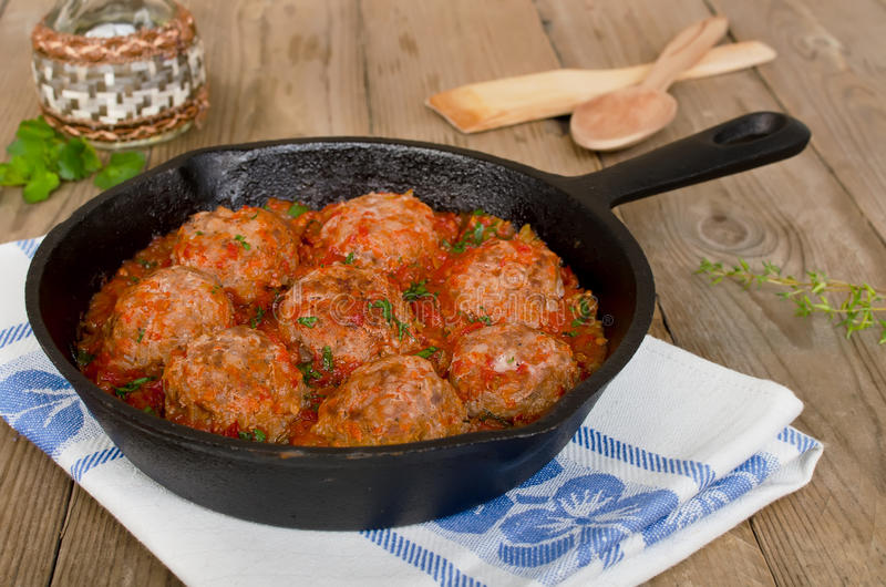 Fried meatballs with tomato sauce and spices in frying pan. On wooden background stock photo