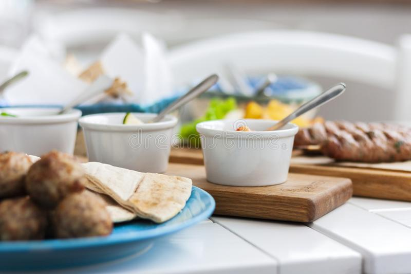 Fried meatballs with white sauce and flat cakes - traditional Greek lunch on a blue plate in a restaurant royalty free stock photography