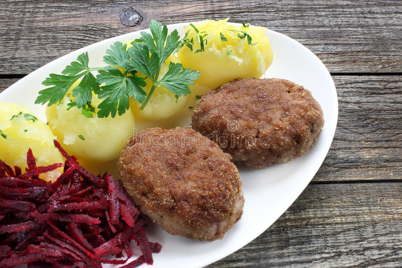 Fried minced pork cutlets. With potatoes and grated red beets royalty free stock images