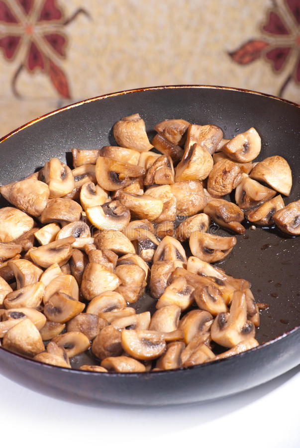 Fried mushrooms in a pan royalty free stock images