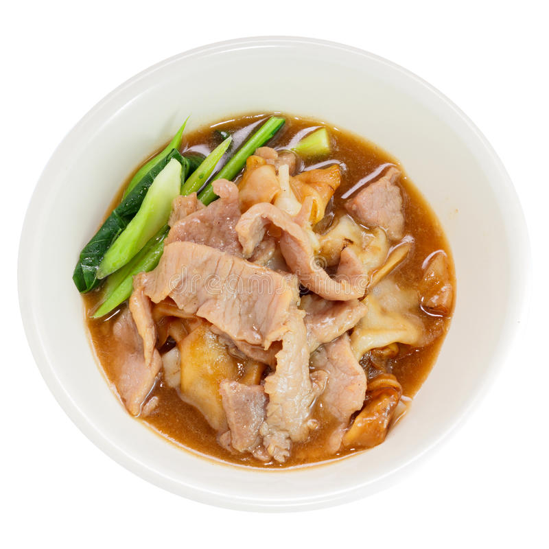 Fried noodle. With pork and kale soaked in gravy, Thailand food on a white round bowl isolated over white background. Top view stock image