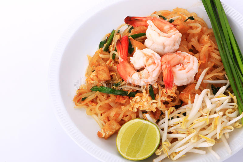 Fried noodle Thai style with prawns, Stir fry noodles with shrimp in padthai style on table. Front view isolate white , brown ba royalty free stock photo