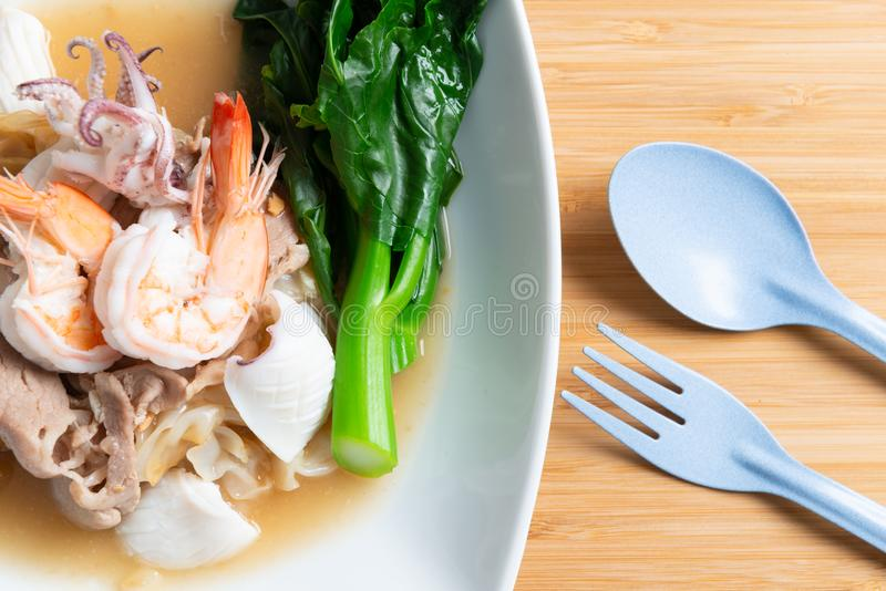 Fried noodles with pork , squid , shrimp and kale in gravy sauce. Thai food call Radna - moo royalty free stock images