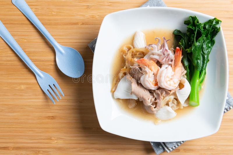 Fried noodles with pork , squid , shrimp and kale in gravy sauce. Thai food call Radna - moo royalty free stock photography