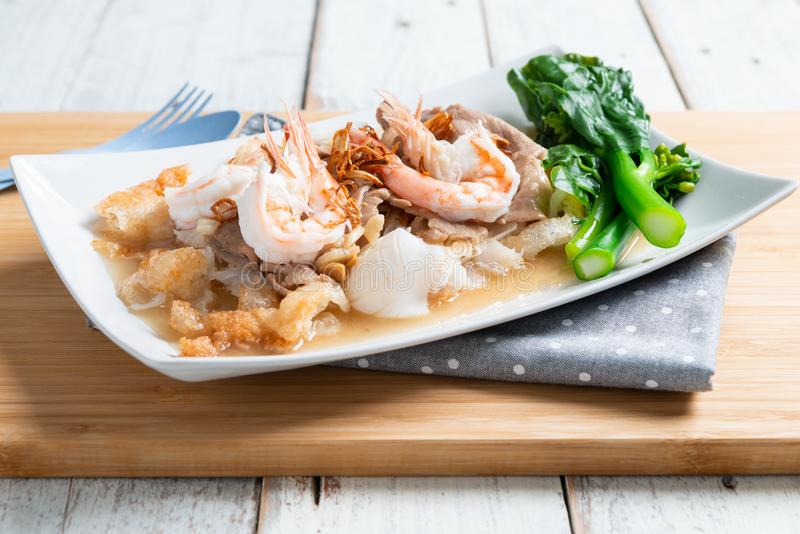 Fried noodles with pork , squid , shrimp and kale in gravy sauce. Thai food call ' Radna - moo stock image
