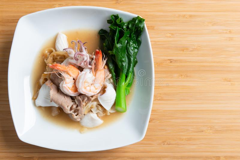 Fried noodles with pork , squid , shrimp and kale in gravy sauce. Thai food call ' Radna - moo stock images