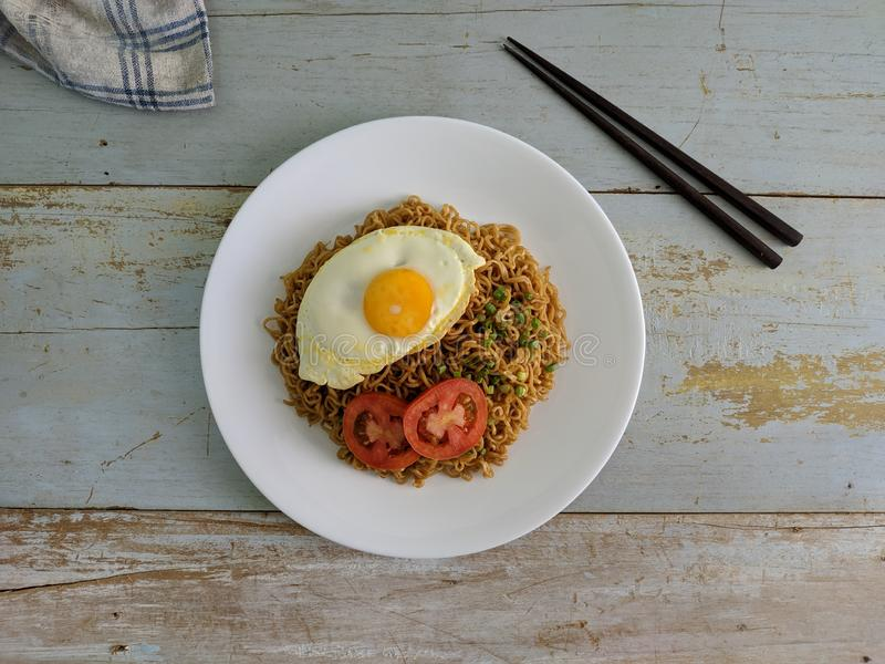 Fried noodles served with fried egg. Food flat lay concept. From top view on wood background stock photography