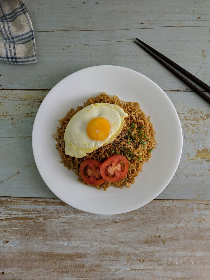 Fried noodles served with fried egg. Food flat lay concept. From top view on wood background stock photo